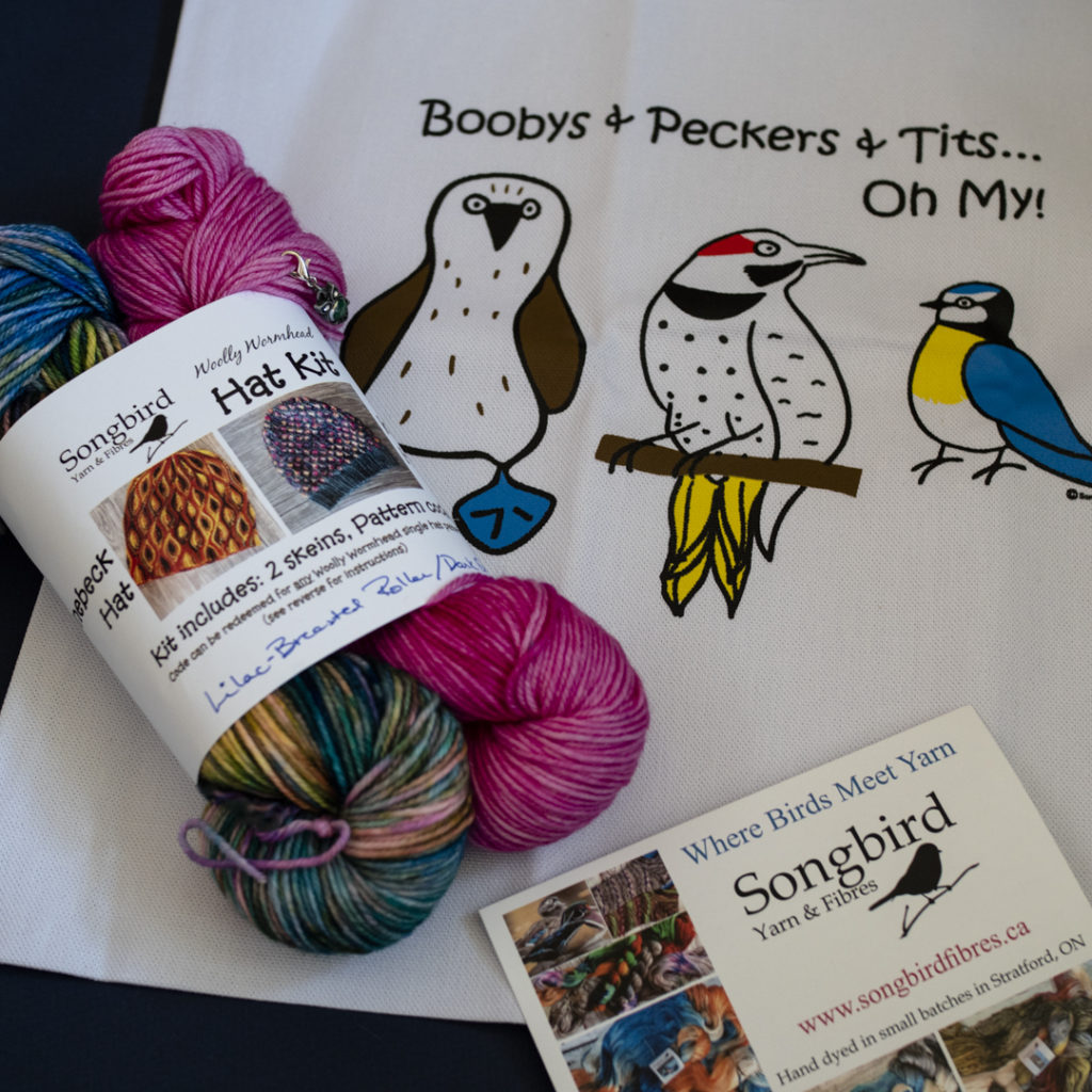 """Songbird Yarn and Fibres gift set with yarn and tote bag. Tote bag has drawings of birds and reads """"Boobys & Peckers & Tits… oh my!"""""""